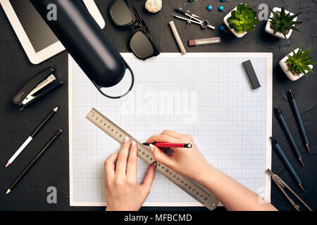 Office desk background hand with pen writing construction project ideas concept, With tablet, drawing equipment and lamp. View from above - Stock Photo