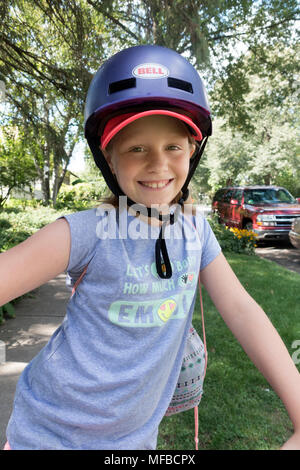 Young girl age 10 smiling and wearing a helmet, ready to start a bicycle adventure. St Paul Minnesota MN USA - Stock Photo