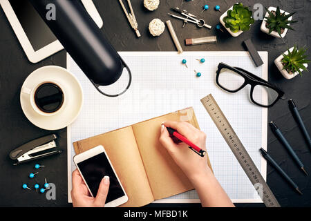 Concept architects. Architects workplace, architectural project, blueprints, ruler. Engineer holds a pen and writes in a notebook. Equipment architects on the desk with a blueprint in the office. - Stock Photo