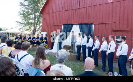 Wedding party lined up in front of barn while minister relates a funny story about his granddaughter. Champaign Illinois IL USA - Stock Photo