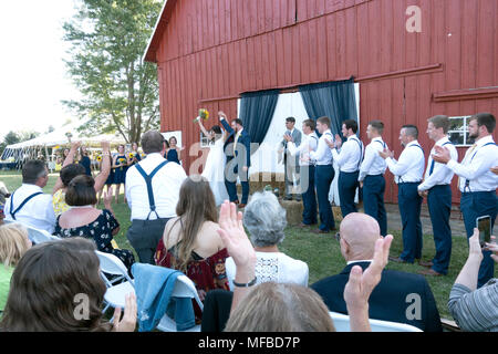 Excited bride and groom raise their arms at the completion of the wedding ceremony in a rural setting with a barn backdrop. Champaign Illinois IL USA - Stock Photo