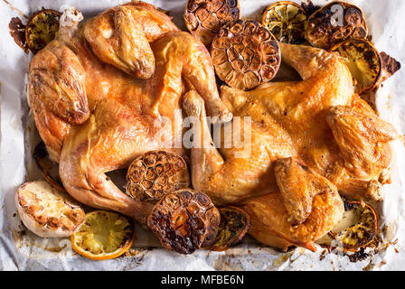 Flattaned out roasted golden chicken with lemon and garlic. Top view. - Stock Photo