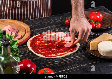 Cook in the kitchen putting the ingredients on the pizza. Pizza concept. Production and delivery of food. - Stock Photo
