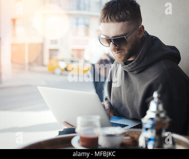 Pensive young man holding laptop on his knees and working on it in cafe. PC and man are on focus and background. Cutlery and tea are on foreground - Stock Photo