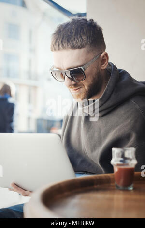Pensive young man holding laptop on his knees and working on t in cafe. Man is on focus and background. Tea is on foreground and blurred. - Stock Photo
