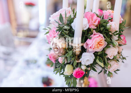 White candles on metal gold candlesticks stand on tables at luxury wedding reception in restaurant. - Stock Photo