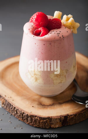 healthy layered raspberry banana smoothie in glass - Stock Photo