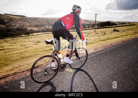 Solo Cyclist riding on a Road in the Brecon Beacon in Wales - Stock Photo