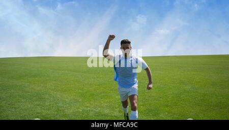 Soccer player on grass with sky - Stock Photo