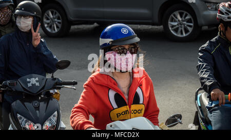 Motorcyclists on motor scooters in stationary traffic wearing face masks to protect against the sun and pollution. Saigon, vietnam, south east asia - Stock Photo
