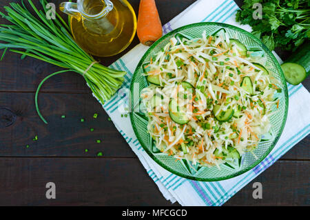Dietary salad with cabbage, cucumber, carrot, greens. Juicy spring salad with fresh vegetables on a wooden table. Proper nutrition. - Stock Photo