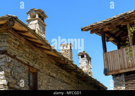 Old authentic rustic houses made of stone bricks and stone slate roofs in Kovachevitsa, Bulgaria against cloudless sky in sunny day - Stock Photo