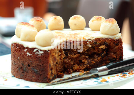 Simnel cake,  traditional at Easter,  on a cake stand with a knife - Stock Photo