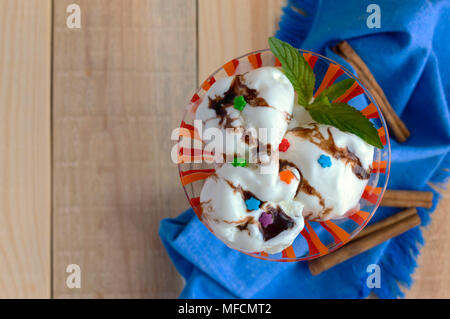 Ice cream, decorated with chocolate syrup and mint in a glass. top view - Stock Photo
