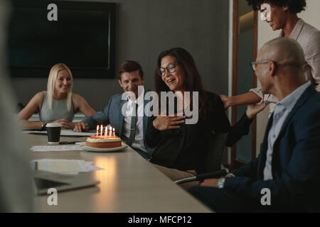 Office workers celebrating female colleague's birthday during a meeting in conference room. Business team celebrating colleagues birthday in office - Stock Photo