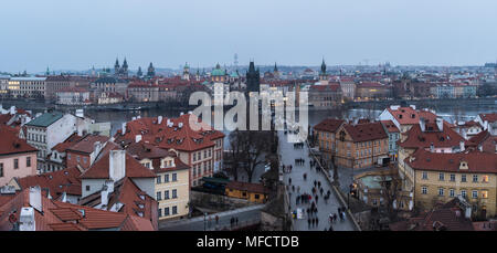High angle panorama of the famous Charles Bridge and the old town tower and churches in Prague, Czech Republic capital city at nightfall - Stock Photo