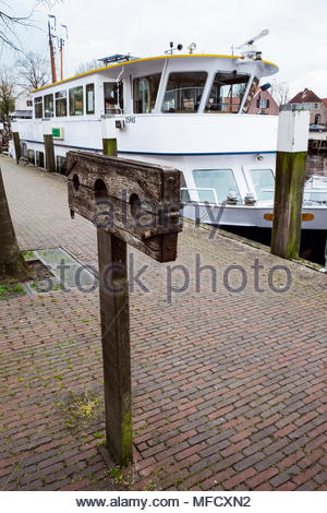 An antique punitive stock stands in the harbor area of the small city of Elburg, in the Netherlands, Rederij Randmeer in background. - Stock Photo