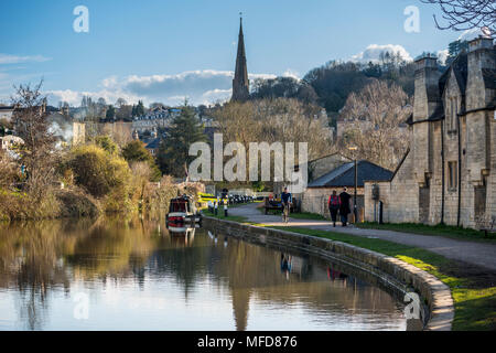 A couple walking and a man riding bicycle along Kennet and Avon Canal, Bath, Somerset, UK - Stock Photo