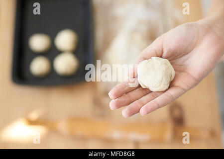 Piece dough in girl hand. Home kitchen - Stock Photo