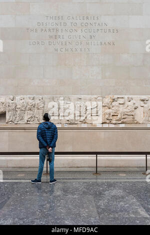 London. England. British Museum, person looking at the Parthenon Frieze (Elgin Marbles), Four Olympian gods seated on stools (central panel), from the - Stock Photo