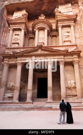 Arab couple looking at the temple carved in the rock of El Hazne, the capital of the Nabataean kingdom, Petra, Jordan - Stock Photo