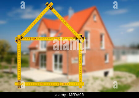 new built house under construction with symbolic yard stick - Stock Photo
