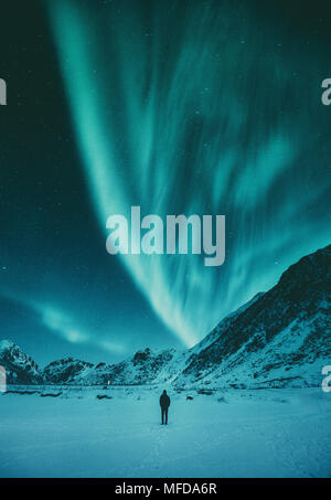 Young man is standing on a remote beach watching the Northern Lights dance above mountains in winter, Lofoten Islands archipelago, Norway, Scandinavia - Stock Photo