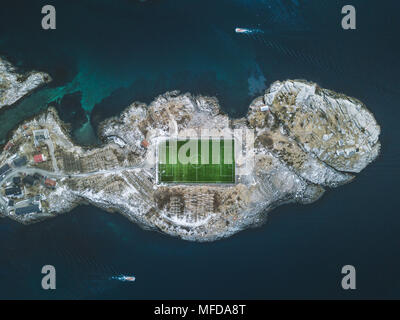 Aerial view of Henningsvaer football stadium with fisherman boats on the Atlantic Ocean, Lofoten Islands archipelago, Norway, Scandinavia - Stock Photo