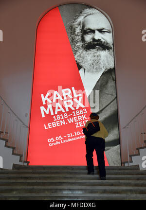 25 April 2018, Germany, Trier: A woman climbing the stairs in front of a poster advertising the large Karl Marx exhibition. According to its organizers, Rhineland-Palatinate's state exhibition 'Karl Marx 1818 - 1883. Life. Work. Times' ist the first ever historico-cultural exhibition on the thinker. It can be seen at the Rheinische Landesmuseum Trier and at the Simeonstift Trier city museum. Photo: Harald Tittel/dpa - Stock Photo