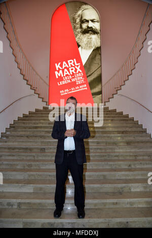 25 April 2018, Germany, Trier: Marcus Reuter, head of the Rheinische Landesmuseum Trier, speaking to media representatives in front of a poster advertising the large Karl Marx exhibition. According to its organizers, Rhineland-Palatinate's state exhibition 'Karl Marx 1818 - 1883. Life. Work. Times' ist the first ever historico-cultural exhibition on the thinker. It can be seen at the Rheinische Landesmuseum Trier and at the Simeonstift Trier city museum. Photo: Harald Tittel/dpa - Stock Photo