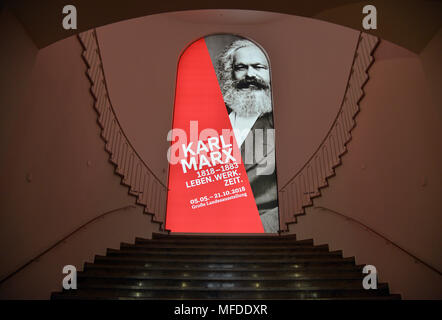 25 April 2018, Germany, Trier: A poster advertising the large Karl Marx exhibition at the Rheinische Landesmuseum Trier. According to its organizers, Rhineland-Palatinate's state exhibition 'Karl Marx 1818 - 1883. Life. Work. Times' ist the first ever historico-cultural exhibition on the thinker. It can be seen at the Rheinische Landesmuseum Trier and at the Simeonstift Trier city museum. Photo: Harald Tittel/dpa - Stock Photo