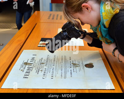 25 April 2018, Germany, Trier: A woman photographs the doctoral certificate of Karl Marx, which was delivered for the large Karl Marx exhibition at the Rheinische Landesmuseum Trier. According to its organizers, Rhineland-Palatinate's state exhibition 'Karl Marx 1818 - 1883. Life. Work. Times' is the first ever historico-cultural exhibition on the thinker. It can be seen at the Rheinische Landesmuseum Trier and at the Simeonstift Trier city museum. Photo: Harald Tittel/dpa - Stock Photo