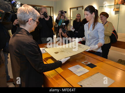 25 April 2018, Germany, Trier: Surrounded by journalists, curator Barbara Wagner (L) and restorator Sarah Bruch place the doctoral certificate of Karl Marx on the exhibition table at the large Karl Marx exhibition at the Rheinische Landesmuseum Trier. According to its organizers, Rhineland-Palatinate's state exhibition 'Karl Marx 1818 - 1883. Life. Work. Times' is the first ever historico-cultural exhibition on the thinker. It can be seen at the Rheinische Landesmuseum Trier and at the Simeonstift Trier city museum. Photo: Harald Tittel/dpa - Stock Photo