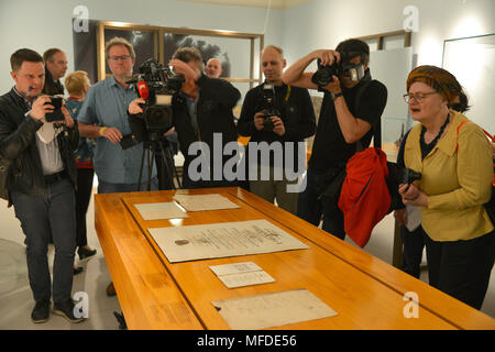 25 April 2018, Germany, Trier: journalists study and photograph the doctoral certificate of Karl Marx at the large Karl Marx exhibition at the Rheinische Landesmuseum Trier. According to its organizers, Rhineland-Palatinate's state exhibition 'Karl Marx 1818 - 1883. Life. Work. Times' is the first ever historico-cultural exhibition on the thinker. It can be seen at the Rheinische Landesmuseum Trier and at the Simeonstift Trier city museum. Photo: Harald Tittel/dpa - Stock Photo