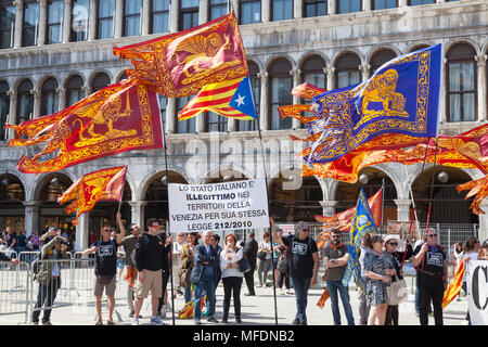Venice, Veneto, Italy. 25th April 2018. Festivities in St Marks Square marking Liberation Day (Festa della Liberazione) commemorating the end of World War II and the Nazi occupation of Italy and Commemorating their fallen soldiers. For Venice it is also the Feast of St Mark (Festa di San Marco) the patron saint of the city marking the anniversary of his death.  Activists for the liberation of Venice from Italy holding a banner and Venetian flags in Piazza San Marco. Credit MCpics/Alamy Live News - Stock Photo