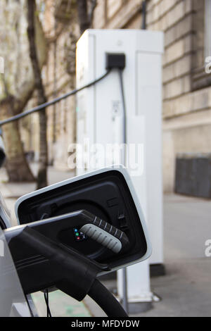 Power supply for electric car charging. Electric car charging station. Close up of the power supply plugged into an electric car being charged. - Stock Photo