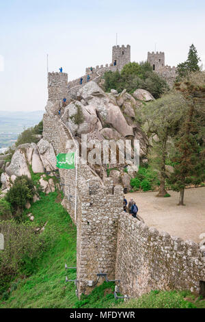 Sintra castle, view of tourists exploring the castle walls of the Castelo dos Mouros (Castle Of The Moors), Sintra, Portugal. - Stock Photo