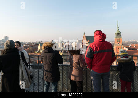 Warsaw, Poland - March 4 2018: Tourists enjoy the view over Warsaw old town from an observatory tower in Poland capital city. - Stock Photo
