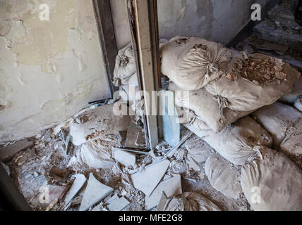 Sand bags and rubbled from inside a bombed out building from Bosnian War in Mostar, Bosnia and Herzegovina - Stock Photo