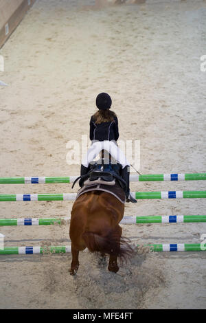 Young child girl rider jumping on the horse over obstacle at show jumping competition - Stock Photo