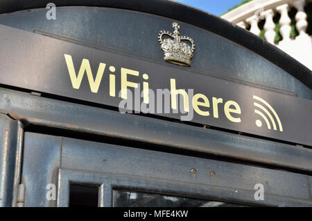 'Wifi here' sign on a public telephone box - Stock Photo