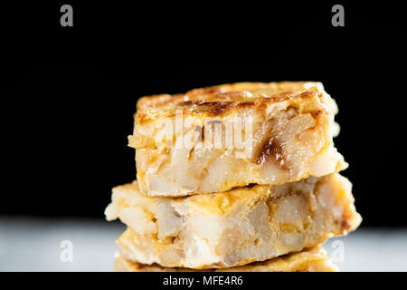 closeup of some pieces of typical tortilla de patatas, spanish omelet, on a rustic wooden table, against a black background - Stock Photo