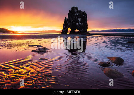 Is a spectacular rock in the sea on the Northern coast of Iceland. Legends say it is a petrified troll. On this photo Hvitserkur reflects in the sea water after the midnight sunset - Stock Photo