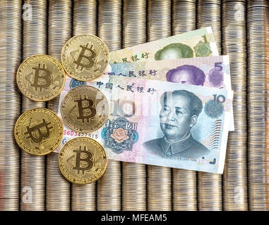 Golden Crypto coins bitcoin BTC, paper Chinese yuan. Metal coins are laid out in a smooth background to each other, close-up view from the top, crypto - Stock Photo
