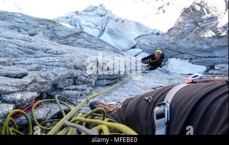 mountain guide on a hard granite climb to a high alpine peak in the Swiss Alps - Stock Photo