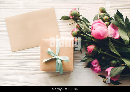 lovely pink peonies with empty craft card and gift box on rustic white wooden background top view, space for text. floral greeting card mock-up. happy - Stock Photo
