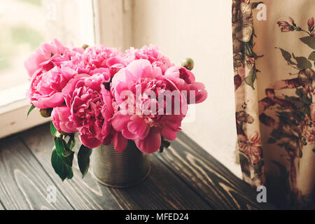lovely pink peonies bouquet on rustic dark wooden background at window light, space for text. top view. floral greeting card. happy mothers day. sprin