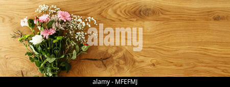 Top view of beautiful handmade bouquet of fresh flowers for Mother's Day placed on wooden table with empty space for your product - Stock Photo