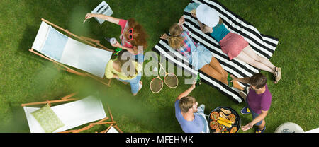 People spending summer time out of town on grilling and having fun - Stock Photo