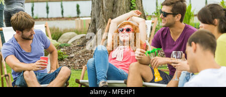 Young happy people chilling and having drinks in the countryside - Stock Photo